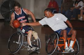 two men playing basketball using sports wheelchairs